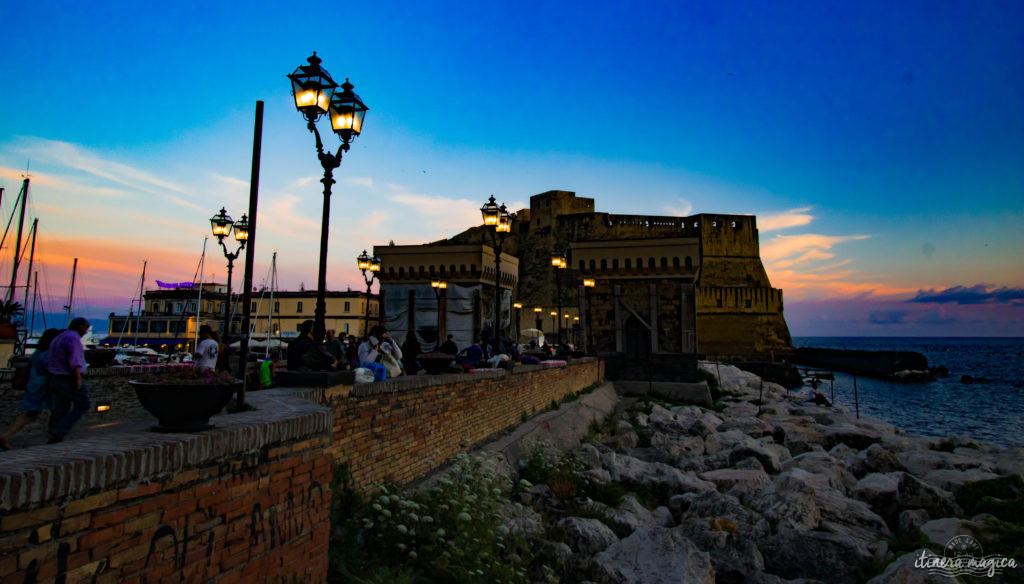 Le Grand Hôtel Vesuvio se détache dans le crépuscule, un palace à l'ancienne, où résonnent les voix des rois, des acteurs et des grands de ce monde qui y ont dormi, depuis 1882. En face, le Castel dell'Ovo, ou château de l'œuf, est un des plus anciens édifices napolitains. Virgile dit avoir enterré un œuf sous ses fondations: tant que l'œuf ne se brisera pas, le château et Naples tiendront debout.