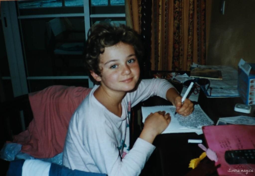 Une photo de moi à l'âge de neuf ans, en Guadeloupe, écrivant mon premier cahier de voyage.