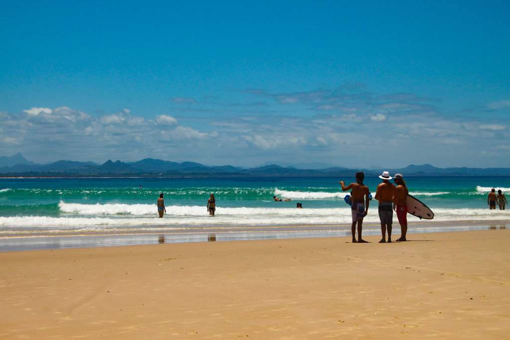 Surfers on the beach in Byron Bay, Australia.